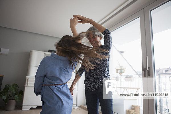 Kleines Mädchen tanzt mit seiner Großmutter zu Hause