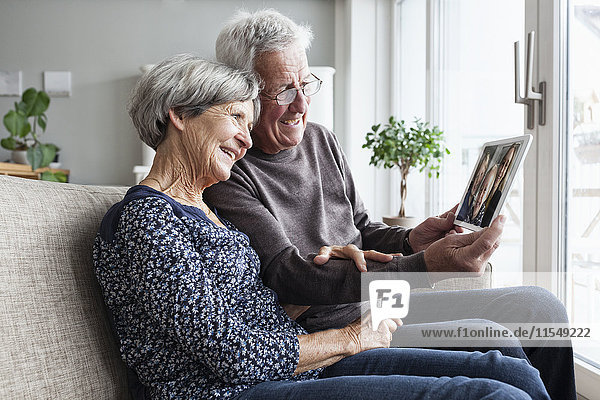 Senior couple sitting in their living room with digital tablet skyping with family