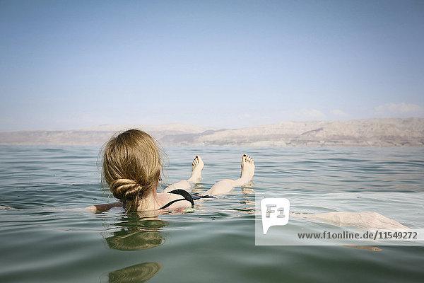Israel  eine Frau  die auf dem Wasser des Toten Meeres schwimmt.