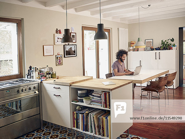 Young man using laptop in open plan kitchen