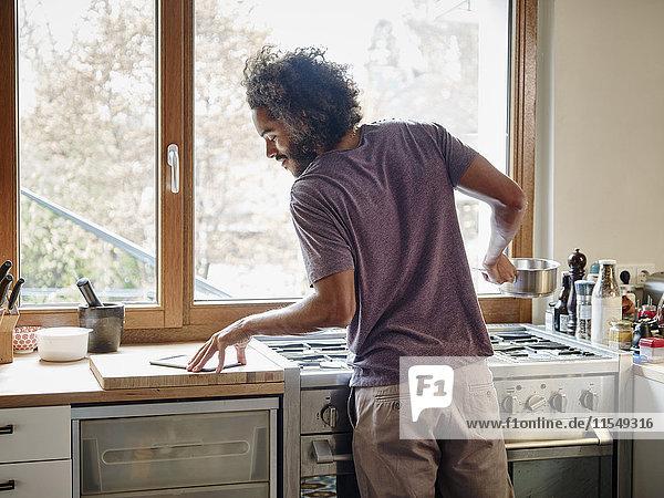 Junger Mann steht am Herd in der Küche und prüft digitale Tablette