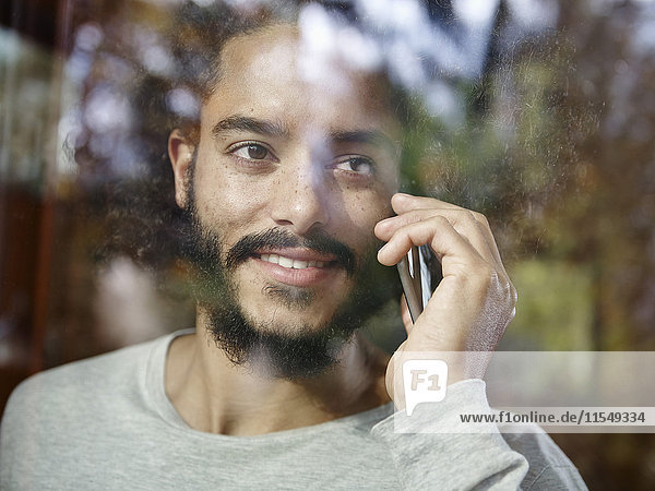 Smiling young man on cell phone behind windowpane