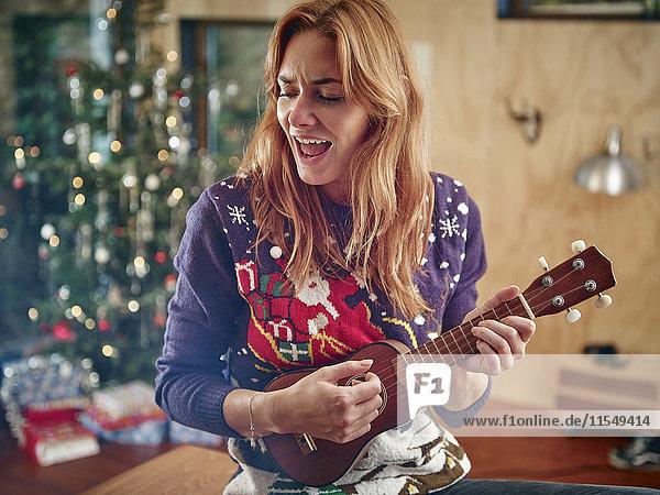 Blonde Frau spielt Ukulele vor dem Weihnachtsbaum