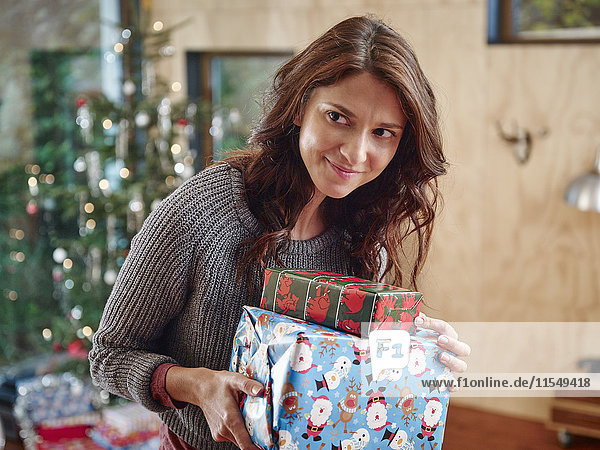 Frau trägt Stapel von Weihnachtspaketen