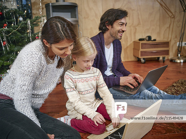 Father using laptop  mother playing with daughter on toy computer on Christmas Eve