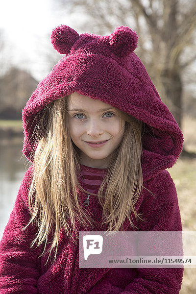 Portrait of smiling girl wearing plush hooded jacket with ears