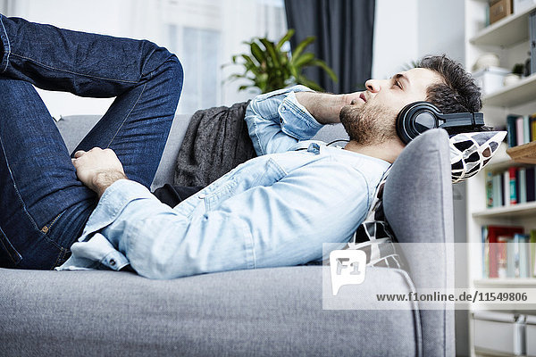 Young man at home lying on couch wearing headphones