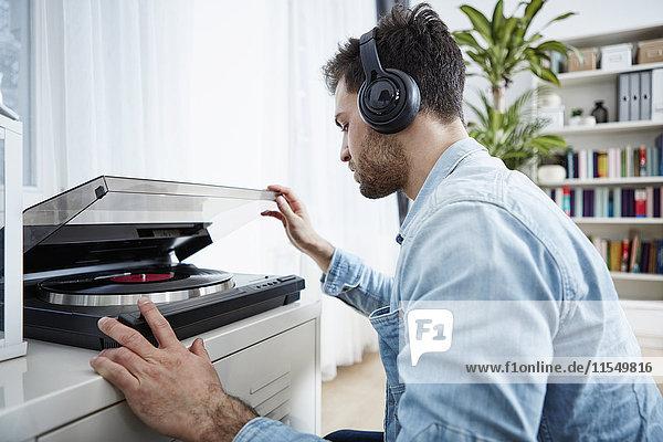 Junger Mann mit Kopfhörer startet Plattenspieler