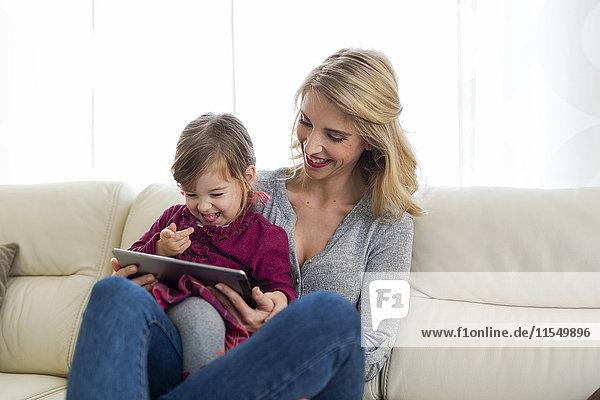 Mutter und ihre kleine Tochter sitzen auf der Couch im Wohnzimmer und schauen auf ein digitales Tablett.