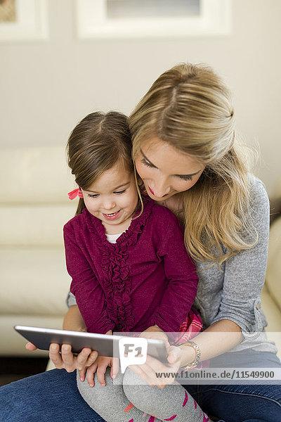 Mother and her little daughter looking at digital tablet