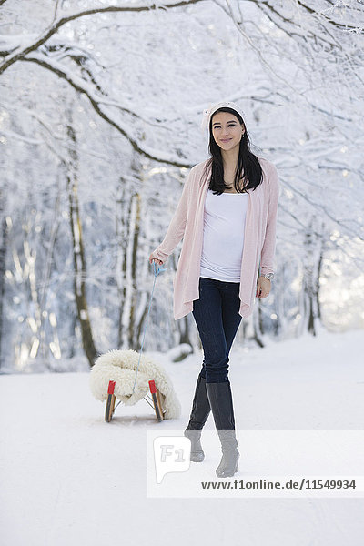 Lächelnde Schwangere im Freien mit Schlitten im Winter