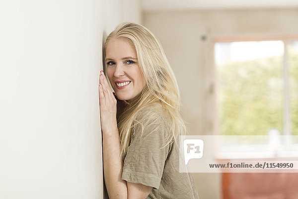 Porträt einer lächelnden jungen Frau  die sich auf der Baustelle an die Wand lehnt.