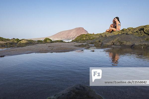 Entspanntes junges Paar auf Felsen am Meer sitzend