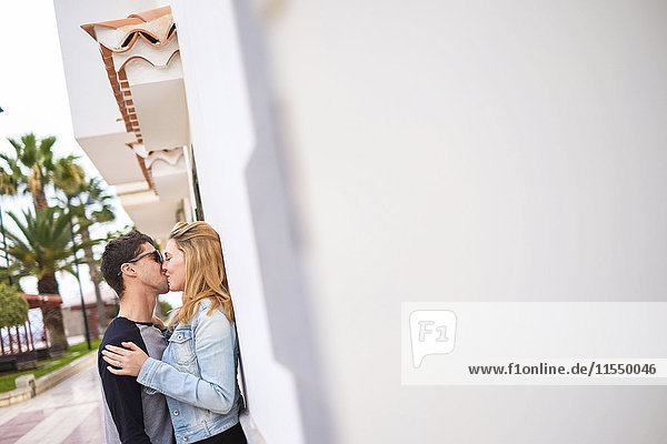 Verliebtes Paar  das sich an einer Wand küsst.