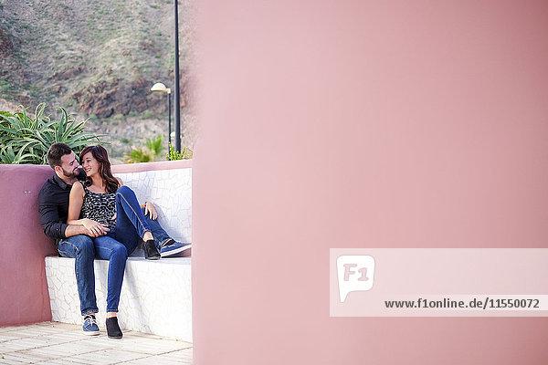 Glückliches junges Paar im Freien sitzend Glückliches junges Paar im Freien sitzend