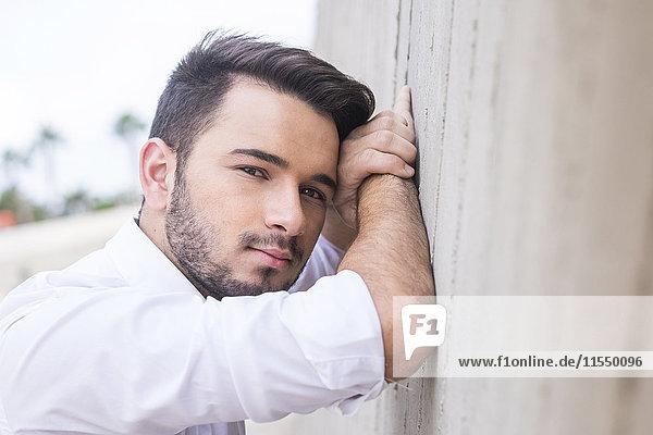 Porträt eines jungen Geschäftsmannes  der sich an die Wand lehnt