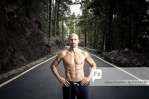 Spanien  Teneriffa  Porträt eines Mannes ohne Hemd mit den Händen auf den Hüften auf einer Straße stehend Spanien, Teneriffa, Porträt eines Mannes ohne Hemd mit den Händen auf den Hüften auf einer Straße stehend