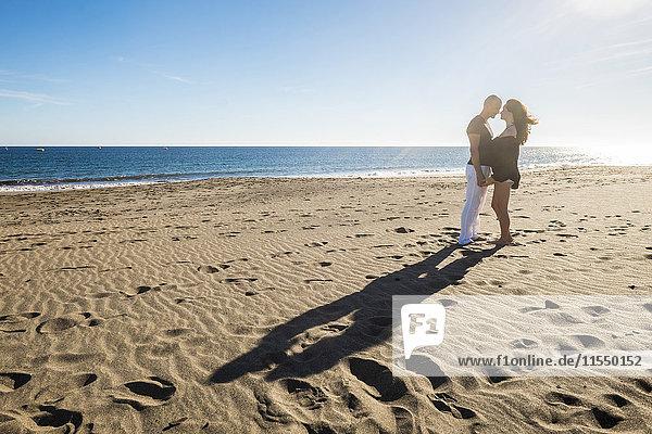 Spanien  Teneriffa  glückliches Paar  das bei Gegenlicht von Angesicht zu Angesicht am Strand steht.