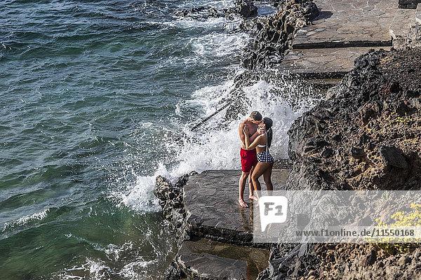 Spanien  Teneriffa  junges verliebtes Paar küsst auf einem Felsvorsprung