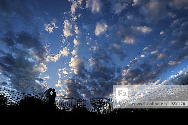 Silhouette eines jungen Brautpaares mit blasendem Brautschleier vor bewölktem Himmel stehend Silhouette eines jungen Brautpaares mit blasendem Brautschleier vor bewölktem Himmel stehend