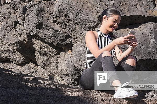 Spanien  Teneriffa  junge Frau sitzt vor einer Felswand und schaut auf ihr Smartphone.