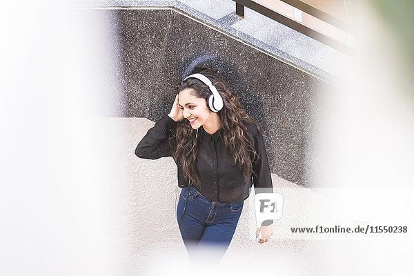 Lächelndes Teenagermädchen beim Musikhören mit Kopfhörern Lächelndes Teenagermädchen beim Musikhören mit Kopfhörern