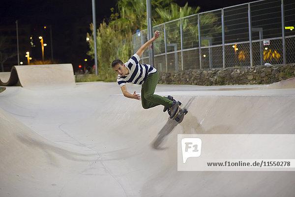Spanien  Barcelona  junger Mann Skateboarding in einem Skatepark bei Nacht