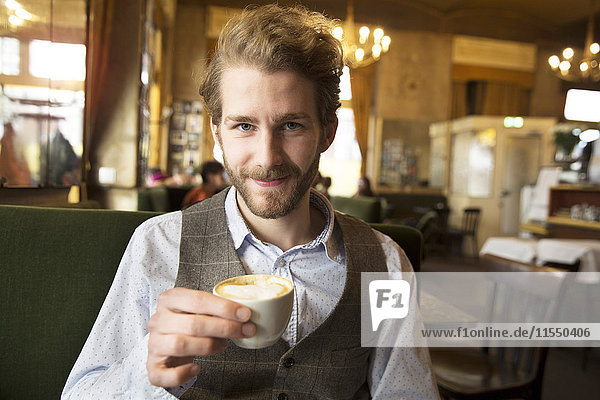 Portrait of smiling young man in a cafe