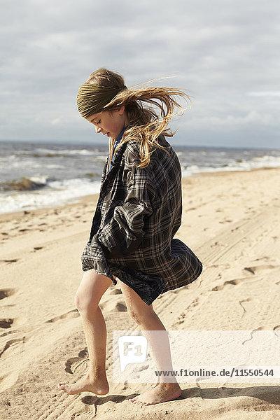 Schweden  Mellby  Mädchen mit blasenden Haaren  das auf dem Hemd ihres Vaters läuft.