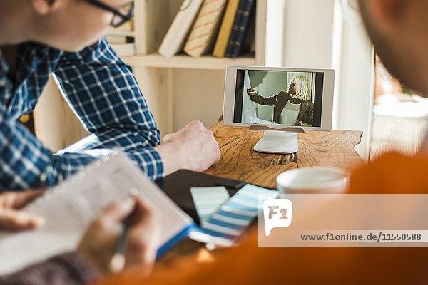Kollegen am Schreibtisch beim Anschauen von Videofilmen auf einem digitalen Tablett