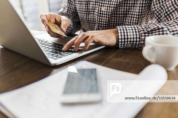 Nahaufnahme des Mannes mit Laptop und Kreditkarte