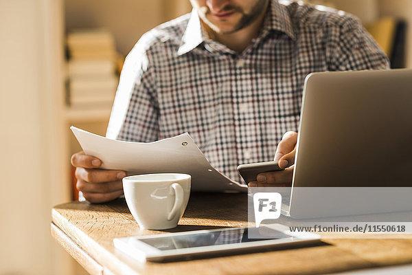 Mann mit Dokument und mobilen Geräten am Schreibtisch