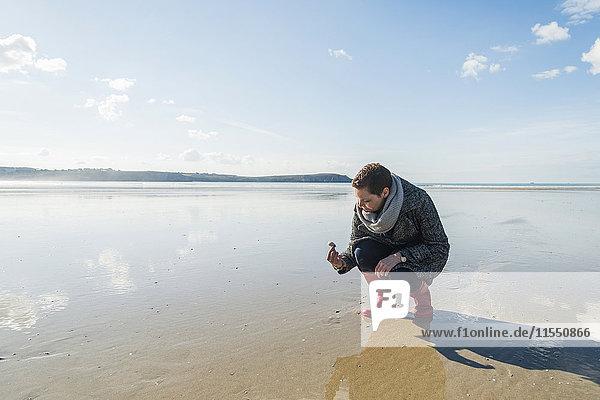 France  Bretagne  Finistere  Crozon peninsula  woman finding a seashell on the beach