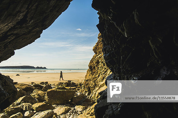 Frankreich  Bretagne  Finistere  Halbinsel Crozon  Frau am Strand von der Felshöhle aus gesehen