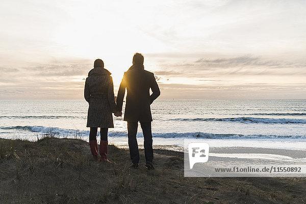 Frankreich  Bretagne  Finistere  Halbinsel Crozon  Paar steht bei Sonnenuntergang an der Küste