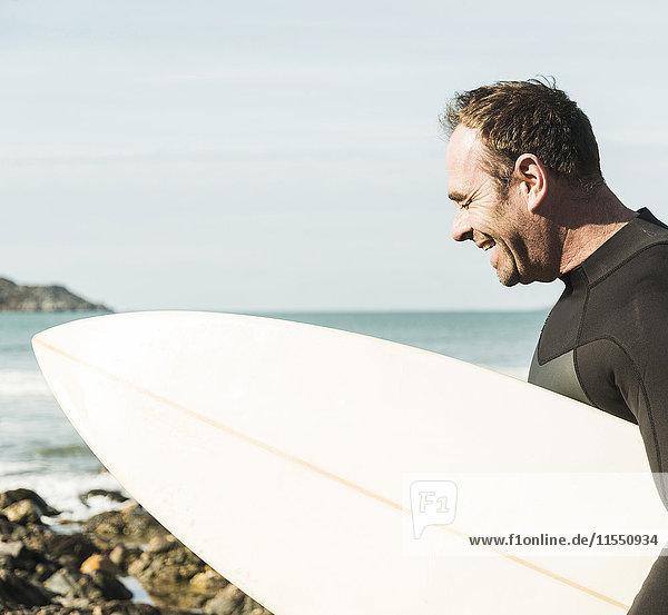 Frankreich  Bretagne  Finistere  Halbinsel Crozon  glücklicher Mann am Strand mit Surfbrett