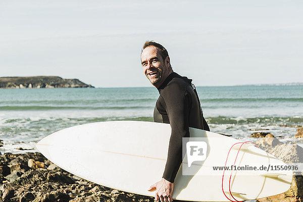 Frankreich  Bretagne  Finistere  Halbinsel Crozon  glücklicher Mann am Felsenstrand mit Surfbrett