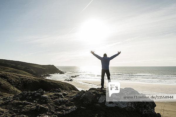 Frankreich  Bretagne  Finistere  Halbinsel Crozon  Mann auf dem Felsen an der Küste mit ausgestreckten Armen