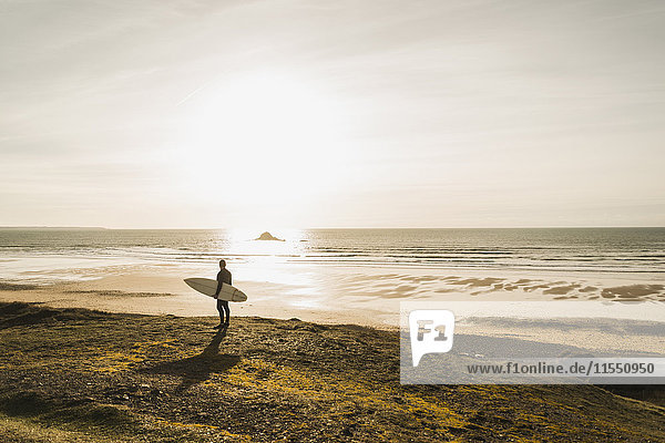 Frankreich  Bretagne  Finistere  Halbinsel Crozon  Mann steht bei Sonnenuntergang an der Küste mit Surfbrett