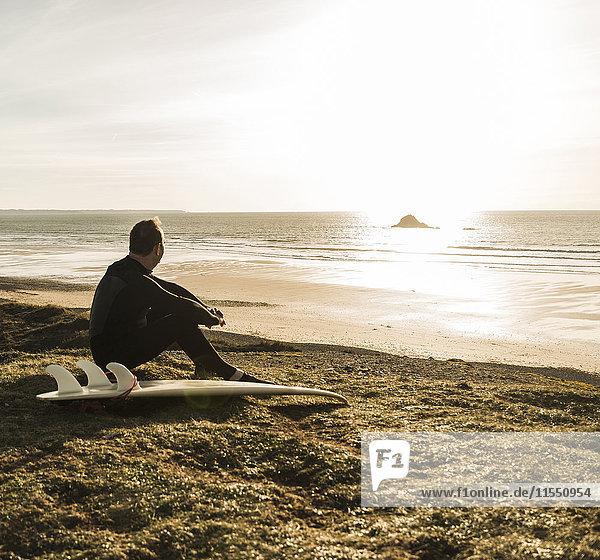 Frankreich  Bretagne  Finistere  Halbinsel Crozon  Mann bei Sonnenuntergang an der Küste sitzend mit Surfbrett