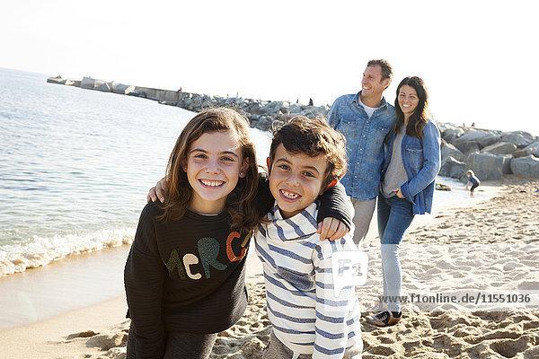 Spanien  Barcelona  Porträt der glücklichen Geschwister am Strand mit ihren Eltern im Hintergrund