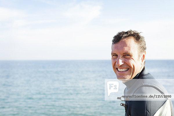 Porträt eines lächelnden Mannes im Neoprenanzug am Meer