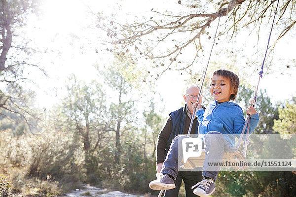Spanien  Siurana  kleiner Junge  der sich auf einer Schaukel amüsiert  während sein Großvater ihn beobachtet.