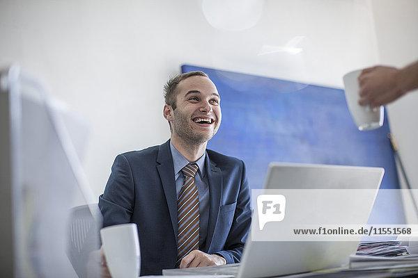 Lachender Geschäftsmann am Schreibtisch mit einer Tasse Kaffee und Blick auf den Kollegen