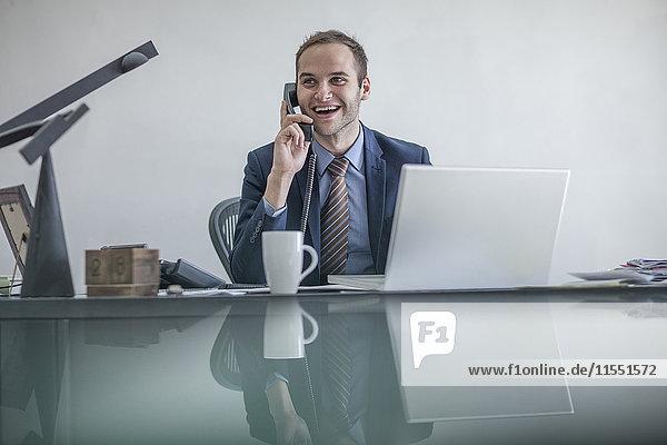 Lächelnder Geschäftsmann am Schreibtisch am Telefon