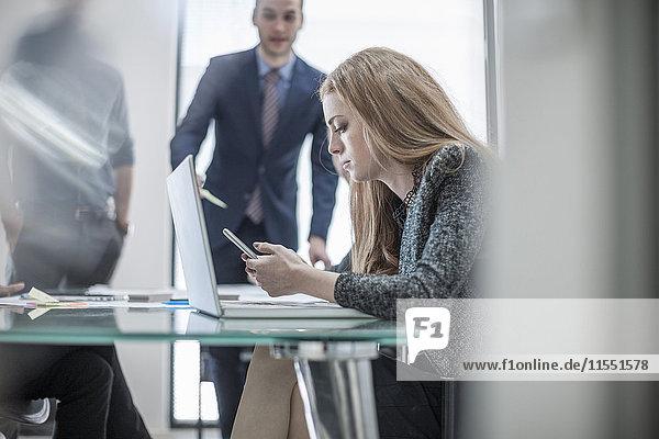 Geschäftsfrau mit Handy und Laptop während einer Besprechung im Konferenzraum