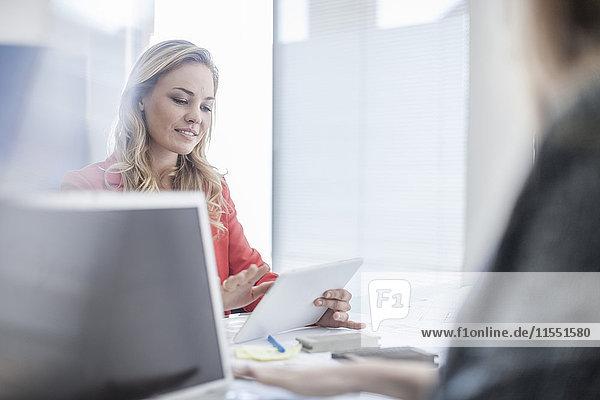 Frau im Büro beim Betrachten des digitalen Tabletts