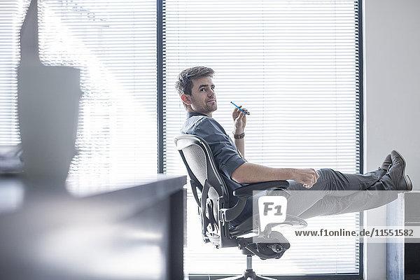 Geschäftsmann im Büro mit erhobenen Füßen