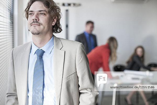 Geschäftsmann am Fenster mit Menschen im Hintergrund
