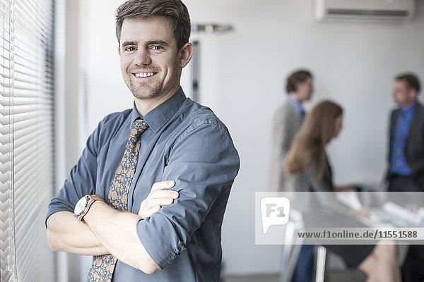 Porträt eines selbstbewussten Geschäftsmannes am Fenster mit Menschen im Hintergrund